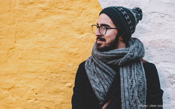 A man with a beard and glasses wrapped in a scarf and beanie.
