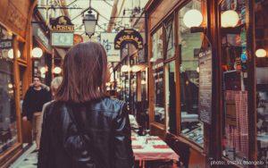 Photo of a woman shopping in a European arcade.