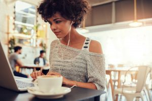 Woman reading a laptop in a coffee shop | Sylvia Adams Websites for Small Business Owners